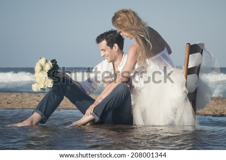 Young beautiful couple enjoying an afternoon flirting and kissing at the beach  - stock photo