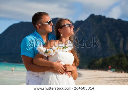 Young beautiful couple enjoying beach getaway. Couple in love, summer luxury vacation in Hawaii, USA. Travel holidays concept. - stock photo