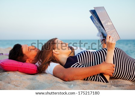 Young beautiful couple have a picnic on the beach. Beautiful pregnant woman reading a book of fairy tales.  - stock photo