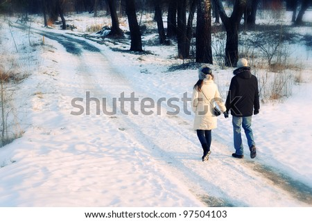 young beautiful couple having a walk in winter park - stock photo