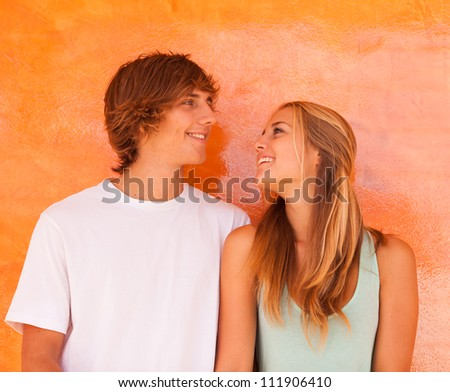 Young beautiful couple having great time over orange background - stock photo