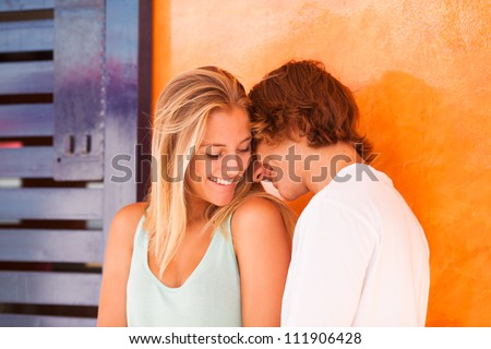 Young beautiful couple having great time over orange background