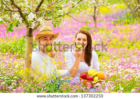 Young beautiful couple having picnic outdoors in summer time, biting fresh green apple, relaxation outdoors, love concept - stock photo