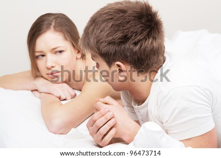 Young beautiful couple in bed having an argument - stock photo