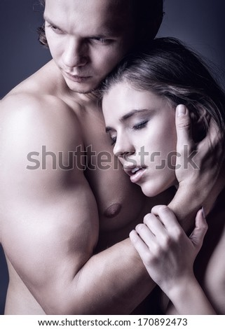 Young beautiful couple in each other's arms on a dark background