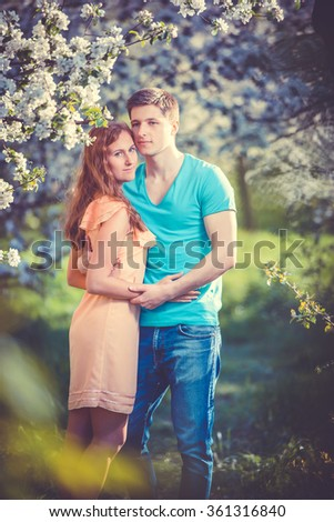 Young beautiful couple in love among apple trees in blossom