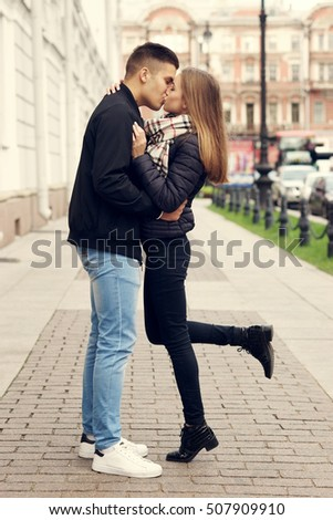 Young beautiful couple in love kissing and hugging at city street on autumn, fall, or spring day. Full length outdoors portrait. Lifestyle.