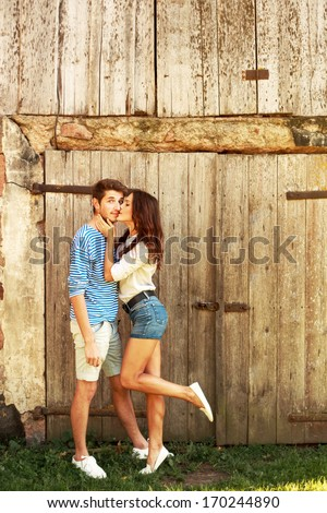 Young beautiful couple in love posing in spring near wooden door having fun and laughing. Girl kiss surprised man vintage style - stock photo