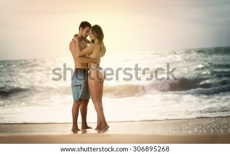 Young beautiful couple in love staying and kissing on the beach on sunset - stock photo