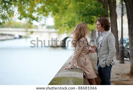 Young beautiful couple in Paris, drinking champagne at the embankment