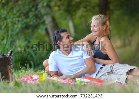 young beautiful couple lying on the lawn in summer park
