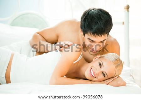 Young beautiful couple making love in bed - stock photo
