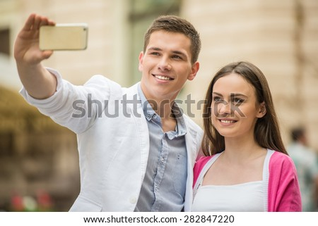 Young beautiful couple making selfie in the street. Romantic date.