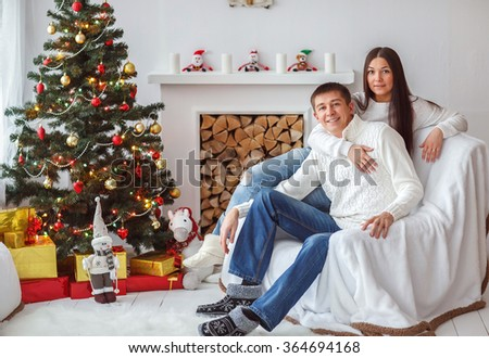 Young beautiful couple playing near a Christmas tree. Loving couple sitting by the fireplace.