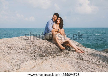 young beautiful couple poses and smiles happily by the sea - stock photo