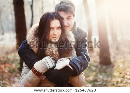Young beautiful couple posing in cold spring forest - stock photo