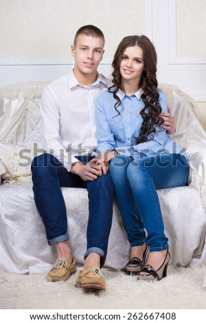 Young beautiful couple posing on the white sofa - stock photo