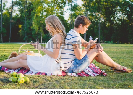 Young beautiful  couple resting in the park and using smarphones