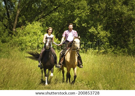 young beautiful couple riding with horse - stock photo