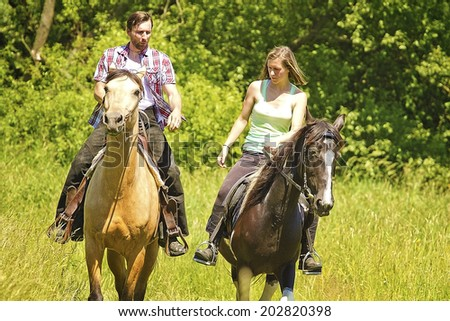 young beautiful couple riding with horse