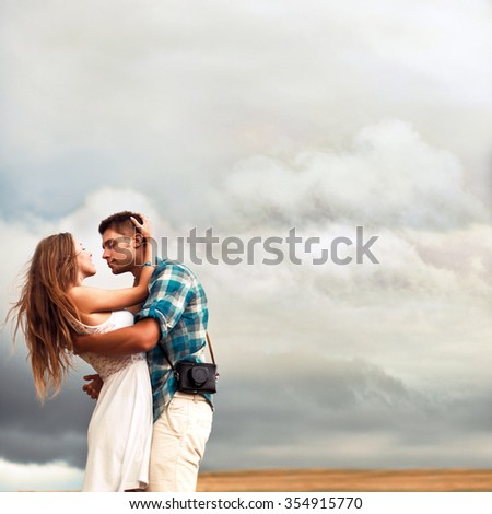 Young beautiful couple sensual style picture posing outdoor in spring on background with sky full of clouds