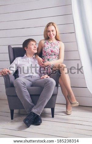 Young beautiful couple sitting on a chair