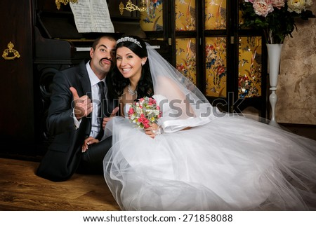 Young beautiful couple sitting on the floor near the grand piano in room - stock photo
