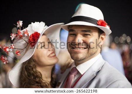 young beautiful couple smiling and laughing while wearing flower hats at the Dubai World Cup Horse Race - stock photo