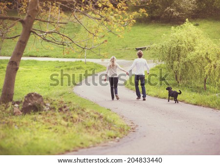 Young beautiful couple taking a walk in green park - stock photo