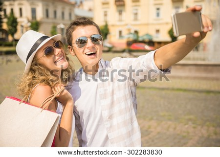 Young beautiful couple taking selfie in the city. Woman holding shopping bags. - stock photo