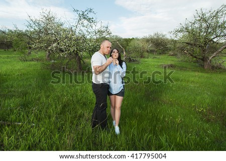 young beautiful couple waiting for a baby standing on a meadow and blowing on dandelions