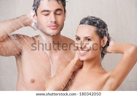 Young beautiful couple washing in the shower - stock photo