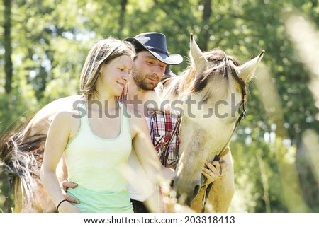 Young beautiful couple with a horse at sunset.