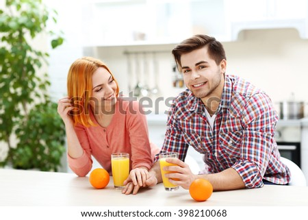 Young beautiful couple with glasses of orange juice in the kitchen