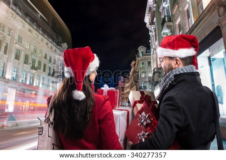 Young beautiful couple with Santa hats in the city