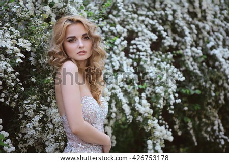 young beautiful curly blonde hair slim girl fashion portrait in white dress posing looking into the camera calm look, in background lush bush with white flowers. Healthy woman lifestyle concept.   - stock photo