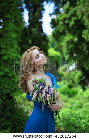 young beautiful curly blonde hair slim girl in blue dress holding bouquet of lupines looking away from camera dreaming in background green park. Healthy woman lifestyle concept - stock photo