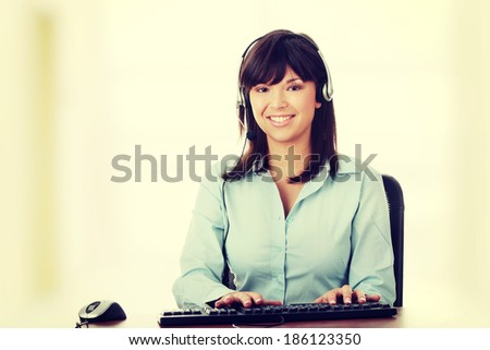 Young beautiful customer service operator girl in headset ,sitting at the desk