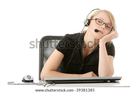 Young beautiful customer service operator girl in headset ,sitting at the desk,tired, isolated on white background. - stock photo