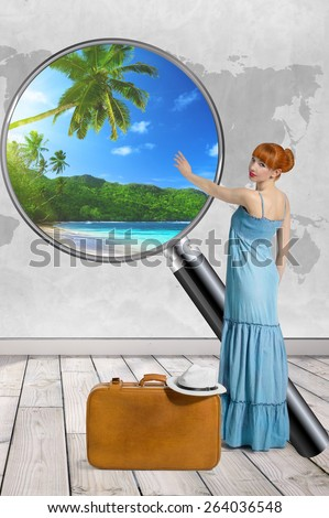 Young beautiful cute optimistic positive happy woman in the blue dress thinking about traveling, tour, summer vacation, trip with suitcase in front of the map background - stock photo