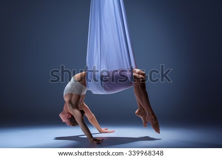 Young beautiful dancer in beige dress posing with  hammock fabric on gray studio background - stock photo