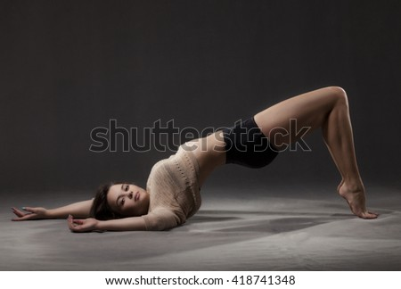 Young beautiful dancer in beige sweater and black short pants posing on a gray studio background - stock photo