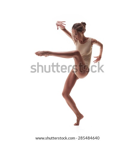 young beautiful dancer in beige swimsuit posing on a isolated white studio background - stock photo