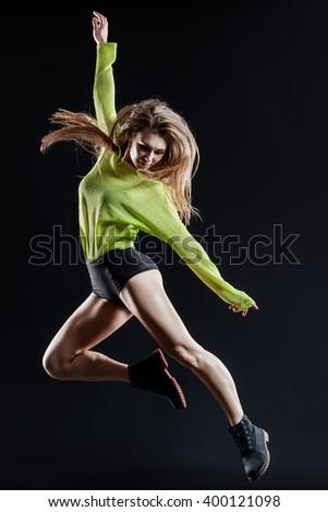 Young beautiful dancer jumping in studio - stock photo