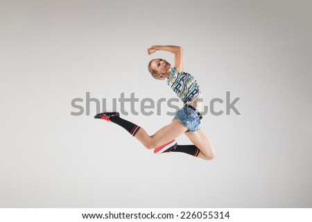 young beautiful dancer jumping in studio grey background