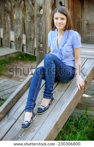Young beautiful dark-haired smiling woman wearing blue blouse and jeans sitting on wooden staircase at summer park. - stock photo