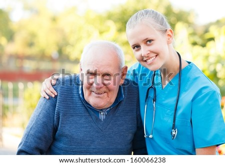 Young beautiful doctor helping his old patient. - stock photo