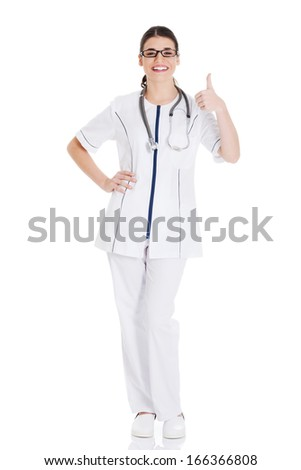 Young beautiful doctor, nurse with stethoscope showing ok. Isolated on white.