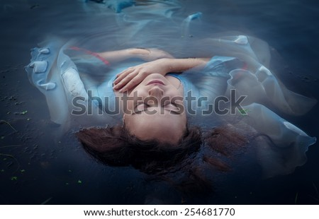 Young beautiful drowned woman in blue dress lying in the water outdoor - stock photo