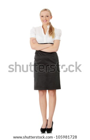 Young beautiful elegant businesswoman is standing with crossed hands and smiling. Isolated on the white background. - stock photo